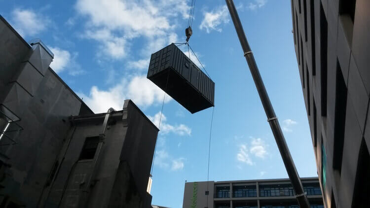 Container Going Over Building   Container Rental & Sales